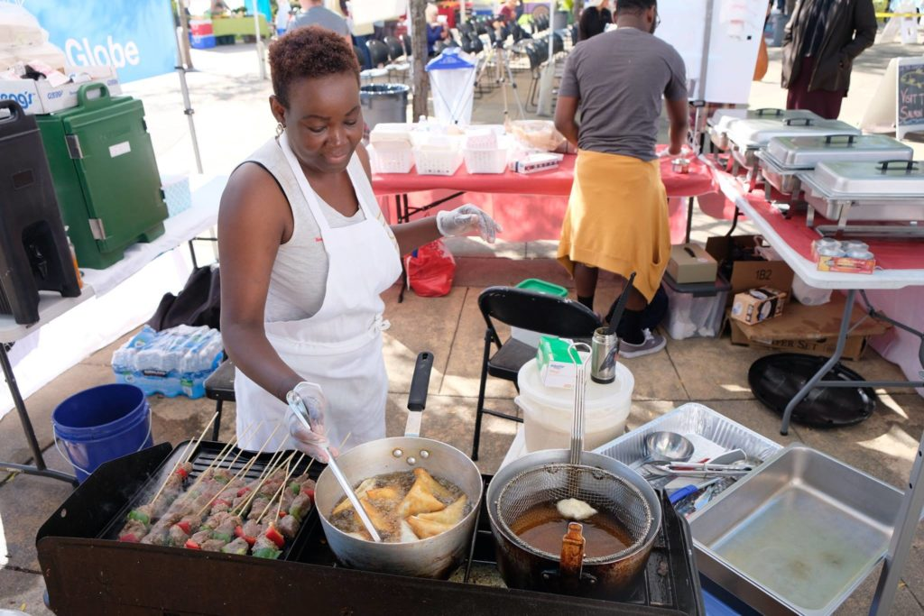 Food Business Incubator participant Caroline launched Taste of Congo in 2018. In this photo, she prepares food to sell at the Renton Farmers Market.
