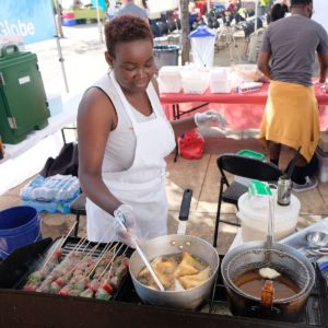 Taste of Congo owner Caroline Musitu prepares food at the Taste Around the Globe booth at Renton Farmers Market.