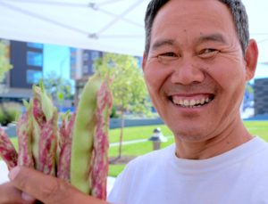 A local food grower holds dragon beans and smiles.