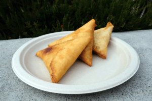 Three crispy, triangle-shaped samosas sit on a plate.