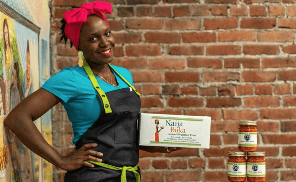 The owner of Naija Buka smiles at the camera and holds a box displaying her business information.
