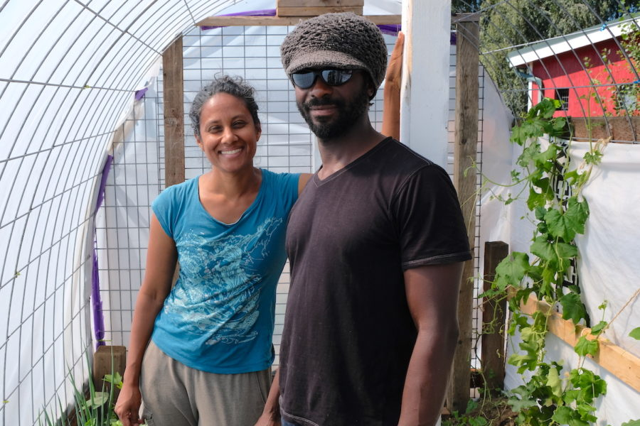 Deepa and Victor stand in a small greenhouse they built