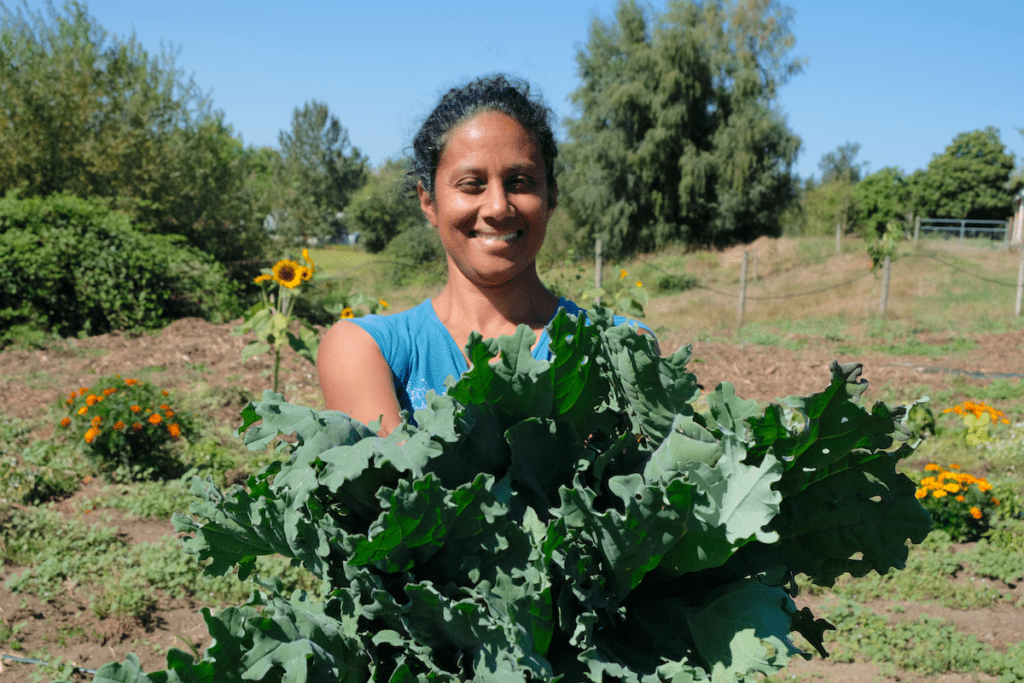 Deepa smiles and holds out kale on a sunny day at Keerai Farm