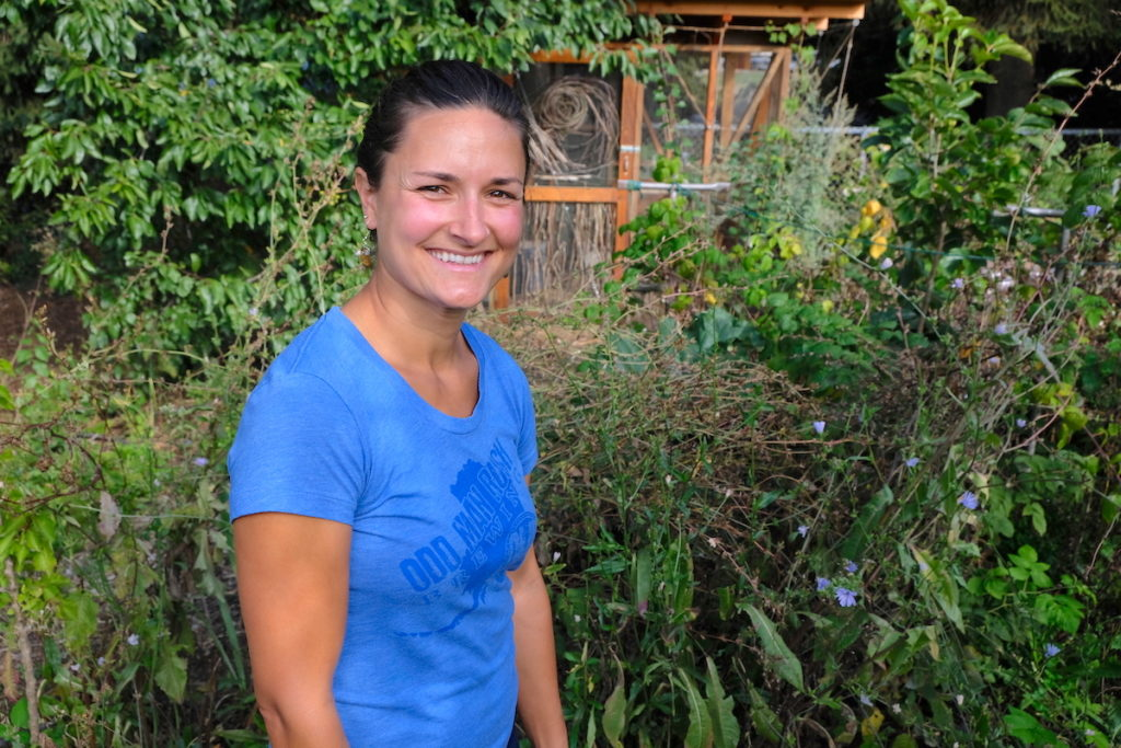 Laura Vogel stands in front of tall green plants and a handmade outbuilding