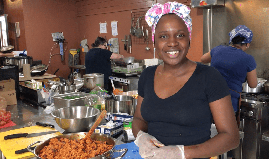 Lilian Ryland smiles at the camera. She stands in a busy kitchen next to a big pot of beans and rice.