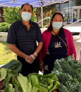 "Two vendors from Namuna Garden wear masks and ""smize"" at the camera. They are standing behind some of the fresh produce they sell at the market."
