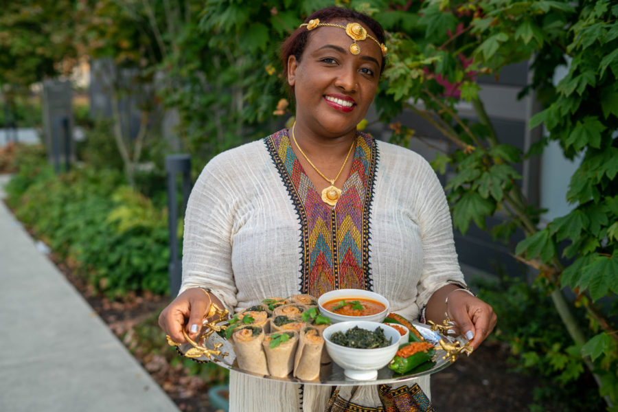 WUHA owner Liyu Wirdaw smiles and holds a platter of Ethiopian-American foods