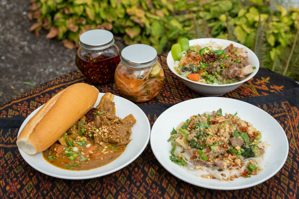 A spread of three authentic Cambodian dishes and two jars of chili oil paste and pickled vegetables