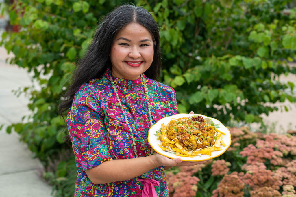 Theary Ngeth smiles and holds a plate of fried rice