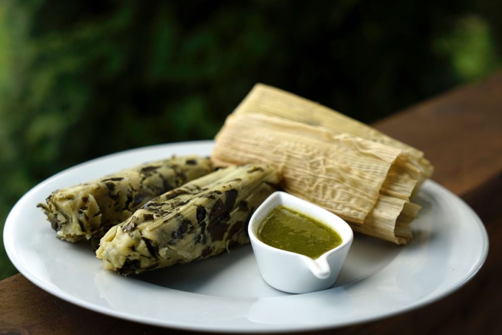 Spinach and cheese tamales and green salsa arranged on a white plate
